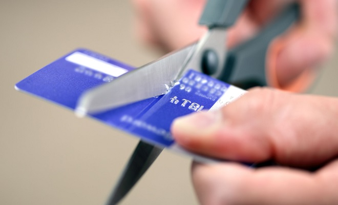 cutting a credit card with scissors | John Kenney & Associates PLLC Kitsap